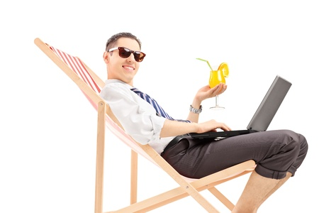 Smiling busy man with laptop sitting on a beach chair and holding a cocktail, isolated on white background photo