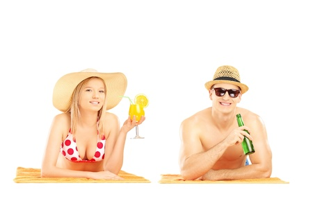 Smiling couple with hats lying on beach towels and posing, isolated on white background  photo