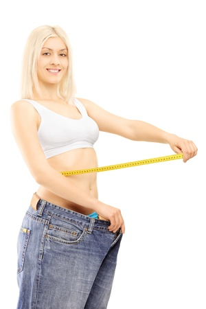 Smiling weightloss woman in old pairs of jeans measuring her waist after diet, isolated on white background photo