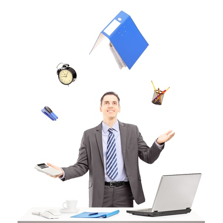 juggling: Young businessman in a suit juggling with office supplies in his office, isolated on white background Stock Photo