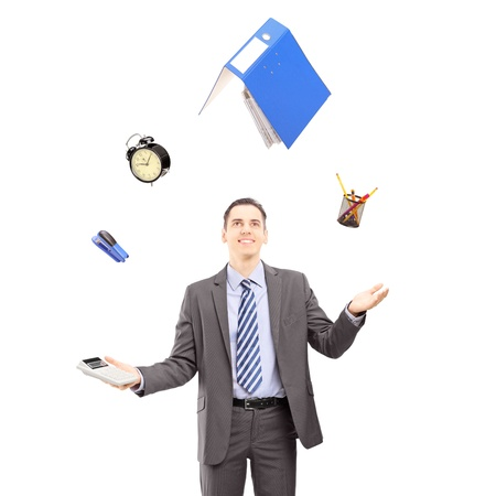 juggling: Young businessman in a suit juggling with office supplies, isolated on white background Stock Photo