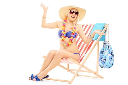 isolated chair: Young happy female with a hat posing on a beach chair isolated on white background