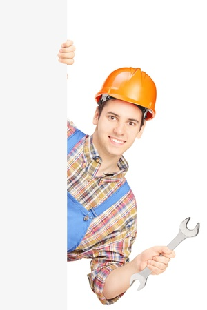 Young manual worker with helmet holding a wrench and posing behind a blank panel isolated on white background photo