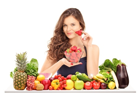 Young smiling female holding a bowl of strawberries and posing behind a table full of vegatebles and fruits isolated on white photo