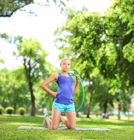 Female athlete on an exercising mat holding a  hoop in a park, shot with a tilt and shift lens photo