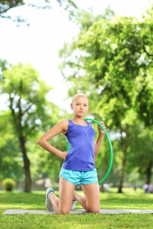 Female athlete on an exercising mat holding a  hoop in a park photo
