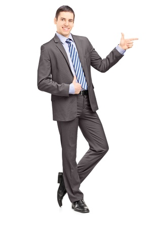 Full length portrait of a young businessman leaning against wall and pointing isolated on white background
