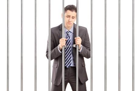 Handcuffed businessman in suit posing in jail and holding bars, isolated on white background photo