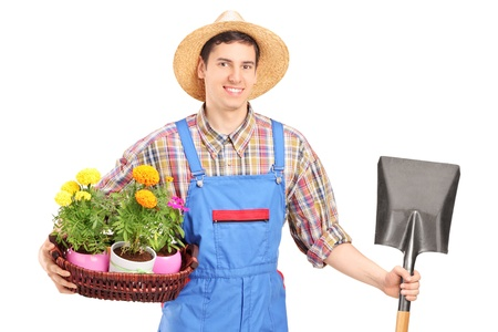 Male agricultural worker holding a shovel and flowers isolated on white background photo