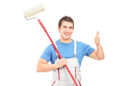 Male painter holding a roller and giving a thumb up isolated on white background Stock Photo - 20470288
