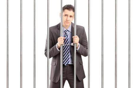 cuffed: Hombre de negocios triste esposado en traje posando en la c�rcel y la celebraci�n de barras, aislado sobre fondo blanco