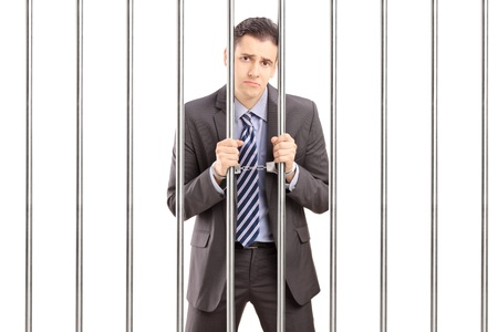 Sad handcuffed businessman in suit posing in jail and holding bars, isolated on white background photo
