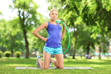 Young female athlete on an exercising mat holding a  hoop in a park photo