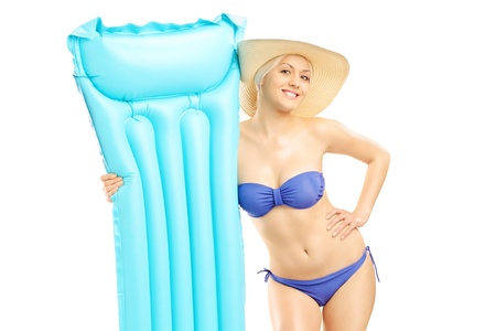 Young woman in bikini holding a swimming mattress, isolated on white background photo