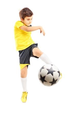 Volledige lengte portret van een jongen in sportkleding schieten een voet bal geïsoleerd op een witte achtergrond