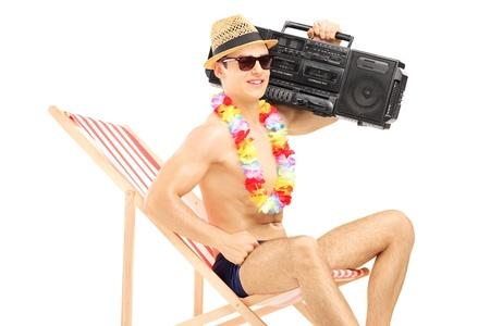 equipo de sonido: Hermoso turística masculino relaja en una silla con el boombox en su hombro, aislado en fondo blanco