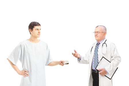 doctor giving dollars: Male patient in hospital gown offering bribe to a medical doctor, isolated on white background Stock Photo