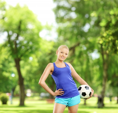 Young active female holding a soccer ball in a park, shot with a tilt and shift lens  photo