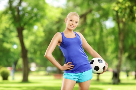 Young smiling female holding a soccer ball in a park photo