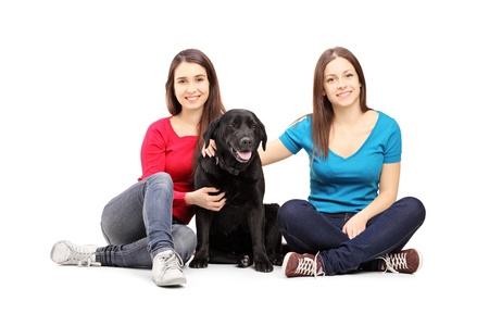 perro labrador: Dos amigas sentado en un piso y posando con un perro negro sobre fondo blanco