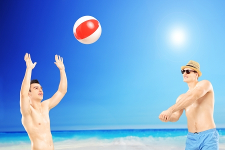 shirtless guy: Young guys playing with a beach ball, next to a sea Stock Photo