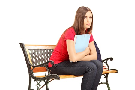 Unhappy female student sitting on a wooden bench with notebook isolated on white background Stock Photo - 20569298