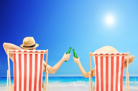 Hombre y mujer que se relaja en una playa y animando con botellas de cerveza Foto de archivo