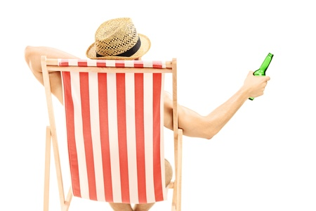 sunbed: Man with hat sitting on a beach chair and holding a beer bottle isolated on white background