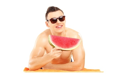 Young man laying on a beach towel and eating a slice of watermelon isolated on white background photo