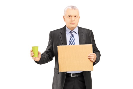 begging: Bankrupted mature businessman holding a piece of cardboard and cup begging, isolated on white background