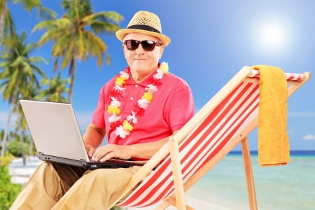 palm computer: Mature male tourist sitting on a sun lounger and working on a laptop, on a tropical beach with palm trees