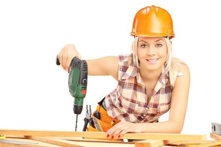 Vrouwelijke timmerman met helm op het werk met behulp van de hand boormachine op een witte achtergrond