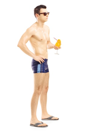 Full length portrait of a guy in swimming shorts holding a cocktail, isolated on white background Stock Photo