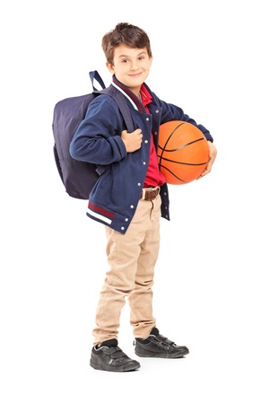 Full length portrait of a schoolboy with backpack holding a basketball, isolated on white background