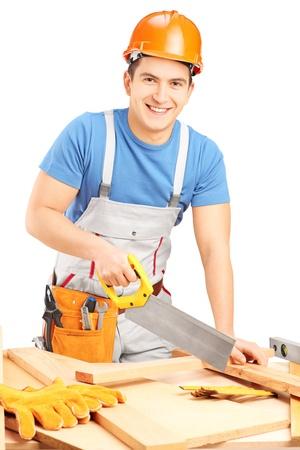 serrucho: Trabajador manual con el casco de corte de listón de madera con una sierra aislada en el fondo blanco Foto de archivo