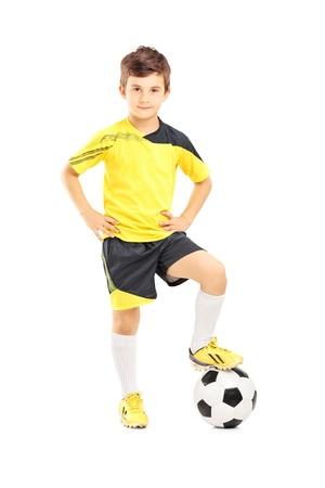 ropa deportiva: Retrato de cuerpo entero de un ni�o en ropa deportiva posando con un bal�n de f�tbol aislado en el fondo blanco Foto de archivo