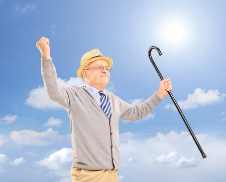 Happy senior man holding a cane and gesturing happiness outside on a sunny day Stock Photo - 20645228