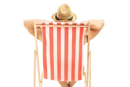 strandstoel: Man met hoed zitten op een strand stoel op een witte achtergrond Stockfoto