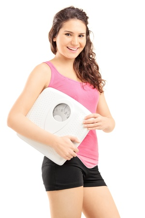 Smiling female athlete holding a weight scale and looking at camera isolated on white background photo