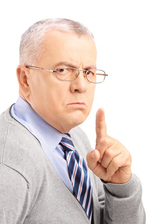 grumpy: Grumpy mature man gesturing silence with a finger isolated on white background Stock Photo