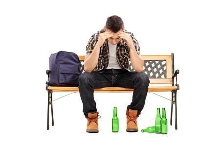 botellas vacias: Hombre joven con resaca sentado en un banco, las botellas de cerveza vacías en el suelo, aislados en fondo blanco