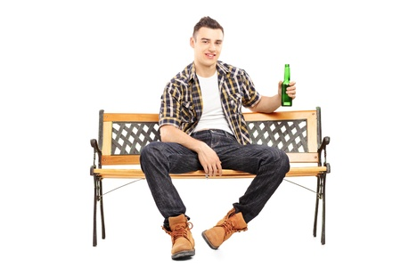 Young smiling man sitting on a bench and holding a beer bottle, isolated on white background photo