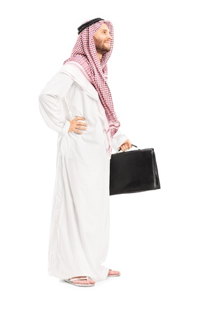 Full length portrait of a male arab person with suitcase posing isolated on white background photo