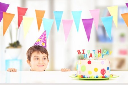 kids birthday party: Smiling boy with party hat looking at a birthday cake at home