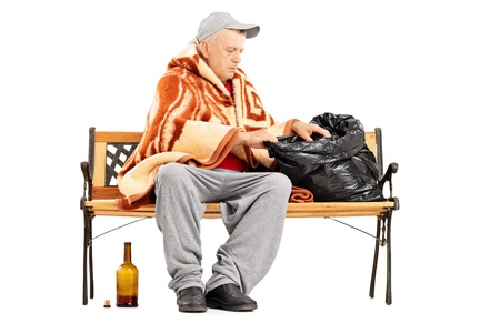 impoverished: Homeless mature man sitting on a bench and looking for something in his bag, isolated on white background