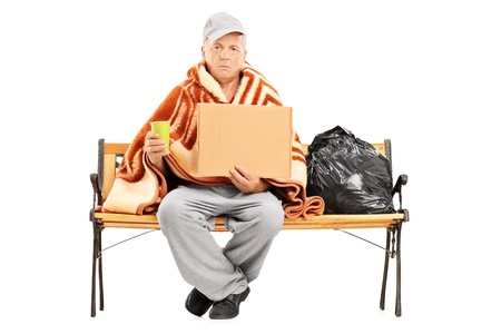 mendicant: Homeless mature man sitting on a bench, his worldly possessions next to him, holding a blank cardboard isolated on white background  Stock Photo