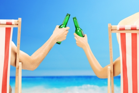 Man and woman relaxing on a beach and cheering with beer bottles, on a beach next to a sea photo