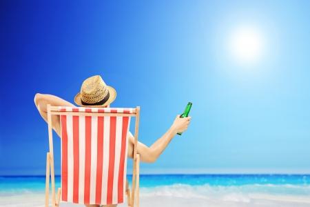 Man met hoed zittend op een strandstoel en die een bierflesje, op een strand naast een zee