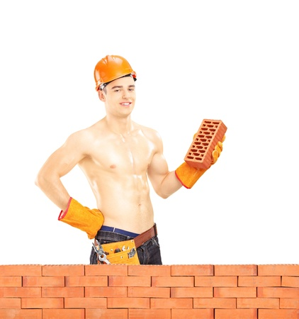 Shirtless muscular male construction worker with helmet holding a brick behind a brick wall isolated on white background, shot with a tilt and shift lens photo