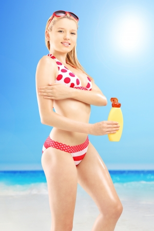 putting in: Young female in bikini putting on sun cream, outside on a beach at sunny day